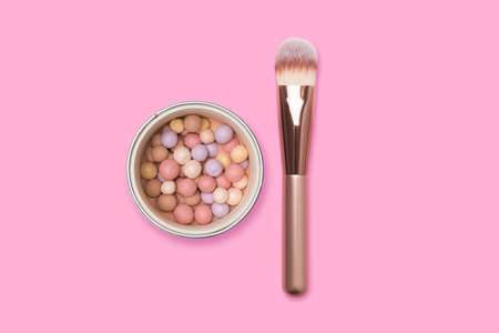 Face powder and brush on a pink background. Meteorites for makeup.