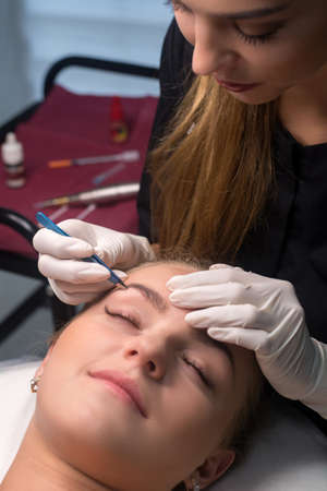 Beautician plucking eyebrows. Eyebrow care in a beauty salon. Фото со стока
