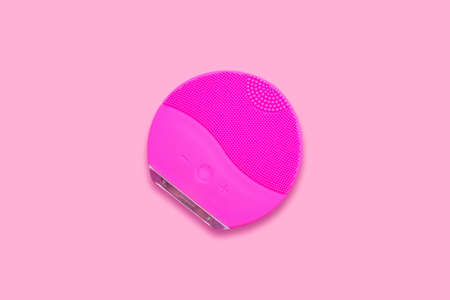 Silicone facial brush on pink background. Beauty gadget.