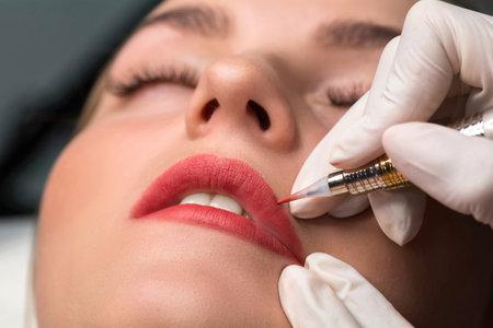 Permanent make up procedure. Lip makeup in tattoo salon.