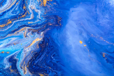 Luxury fluid art painting background. Spilled blue, white and gold acrylic paint. Liquid marble. Alcohol ink splash.