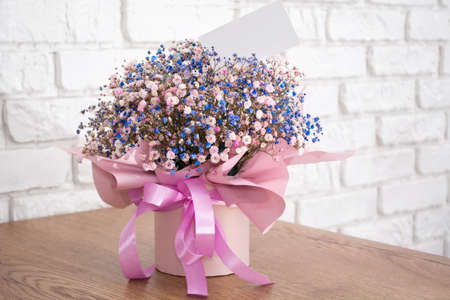 A bouquet of delicate small flowers in a box with a note.