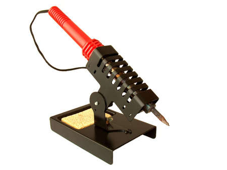 A soldering iron standing on the holder. It is used to assembly and repair electronic products, by melting the solder that keeps micro-electronic components in place. Stock Photo