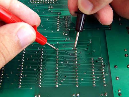 test probe: Tecnico azienda conduce test di risoluzione dei problemi un circuito stampato.  Archivio Fotografico
