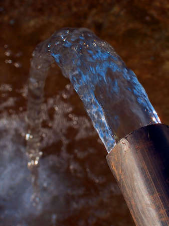 Water flowing from a flexible black plastic water pipe.