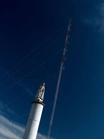 Statue of Our Lady of Fatima in front of an antenna tower. photo