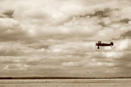 World War II fighter flying at low altitude, performing a fly-by. The ground is not totally crisp because of a slight panning while taking the photo. No sharpening was applied. photo