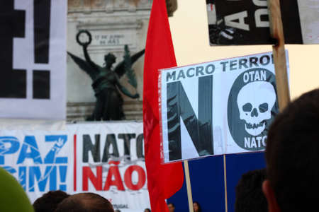 LISBON - NOVEMBER 20: Protesters hold signs with messages against NATO, as they march in the pacific demonstration promoted by anti-NATO organizations, on 20 November 2010, last day of NATO Summit.