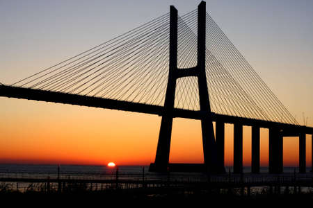 lisbonne: Vasco da Gama bridge, backlit by a mid June sunrise, at Lisbon, Portugal. Image unsharpened. Stock Photo