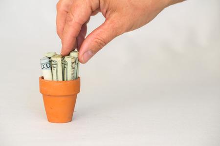 terracotta: Hand putting money in terracotta pot