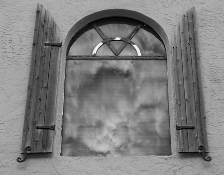 Window on a concrete building with wood shutters Stock Photo