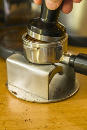 bayonet: tamping the espresso grounds after dosing and leveling into a bayonet