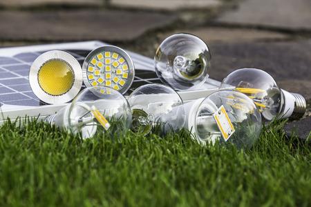 E27 Wolfram, Halogen und verschiedene LED-Lampen auf dem Rasen; GU10 auf Solarpanel Standard-Bild - 32575523