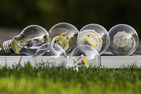 e27: various E27 bulbs, LED, halogen and tungsten bulb on solar panel, some on the grass  ( selective focus )