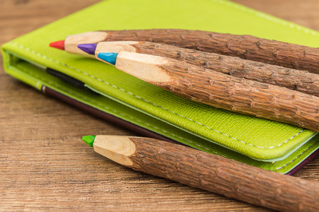 workbook: colored wooden pencils and green brown leather workbook