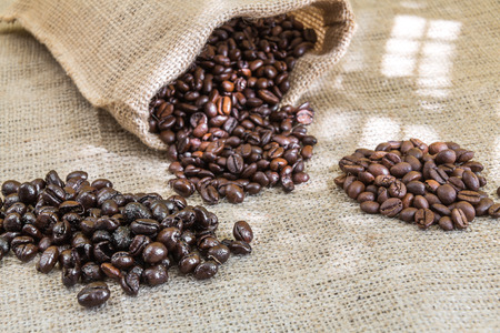 three samples pure Arabica coffee beans of various origins and different roasting on burlap Stock Photo