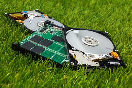 new SSD between two old HDD to the green grass Stock Photo