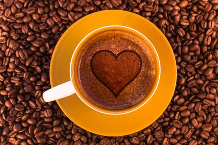 Herz auf frischem Espresso mit einer schönen Crema und verstreuten mittelröstlichen Kaffeebohnen Standard-Bild - 74885105