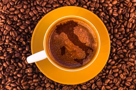 Karte von Italien auf frischem Espresso mit einer schönen Crema und verstreuten mittelröstlichen Kaffeebohnen Standard-Bild - 74888866