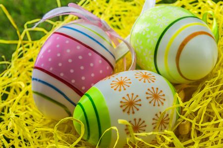 Verzierte gemalte Ostereier auf gelbem Stroh- und Frühlingsgras Standard-Bild - 75468148