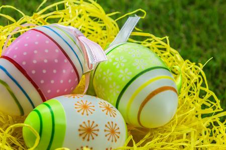 Bemalte dekorierte Ostereier auf gelbem Stroh und Frühlingsgras Standard-Bild - 75460185