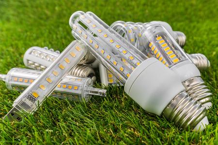 componentes: varios tipos de bulbos ecológicos y económicos del LED (forma similar de E27 como CFL) en la hierba verde Foto de archivo