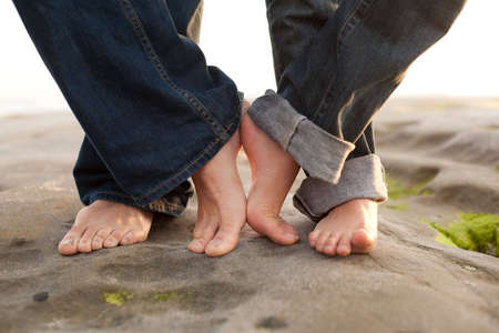 bare women: a couples feet touch on the beach