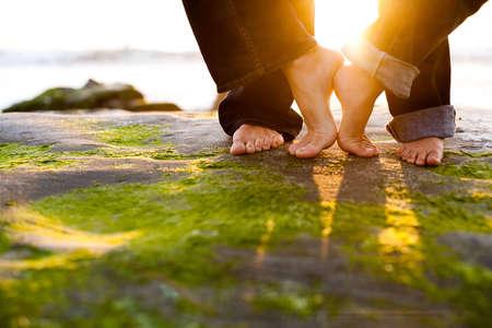 a couples feet embrace on the beach in the sun