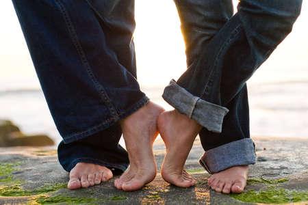 a couples feet on the beach