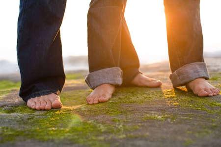 a couples feet on the beach Imagens