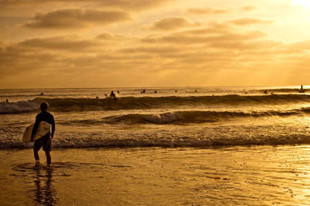 A surfer heads out with a shortboard while surveying a sunset.