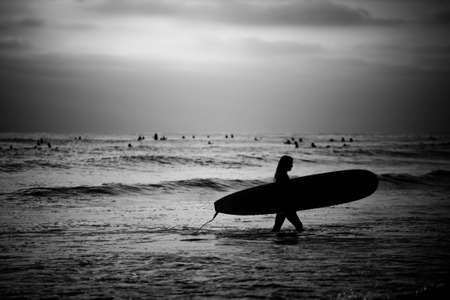 A black and white image of a female surfer searching for an area to surf.