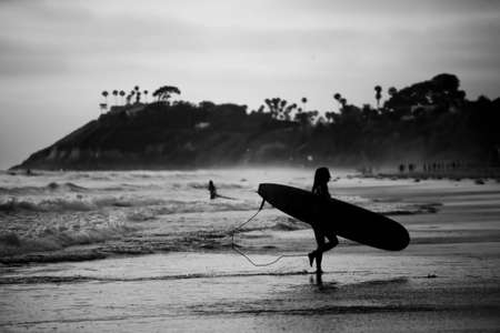 A black and white of a female surfer leaving the beach with a board