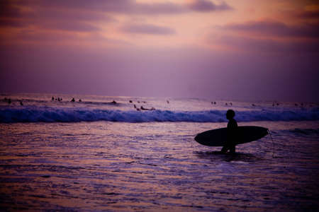 A surfer heads out early in the morning during the sunrise. Imagens