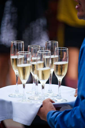 A server carries champagne to party guests