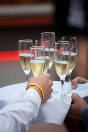 A person takes a glass of cold, golden champagne