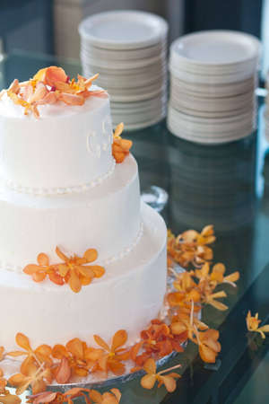 A lovely cake decorated with flowers sitting on a glas table with plates
