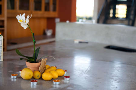 A marble counter with lemons, orchid and candles Imagens