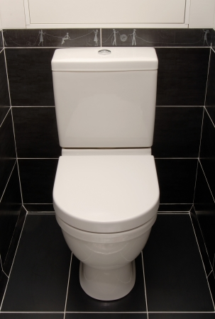 The white toilet bowl is in a black interior  photo