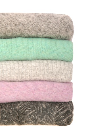 It is a pile of different sweaters  photo
