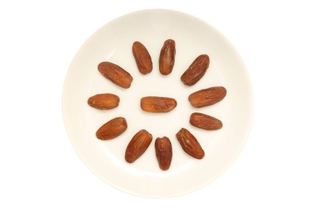 dates fruit: Some dried dates are on white  plate  Stock Photo