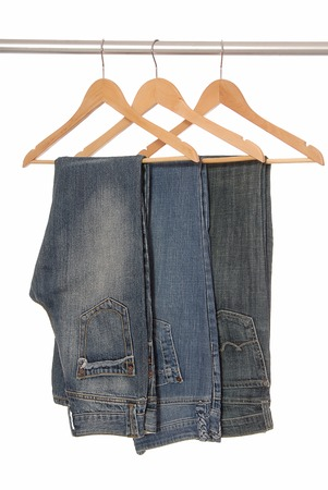 Different  jeans are on woody hangers