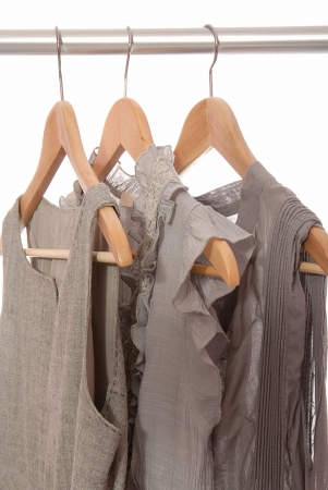 Grey dresses are on wooden hangers  photo