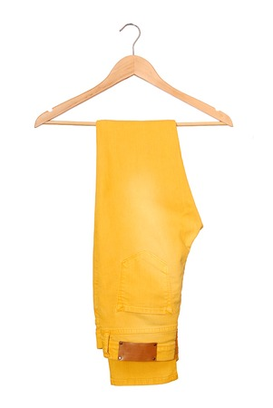 A yellow jeans are on hanger