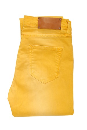 Folded yellow jeans are on white background