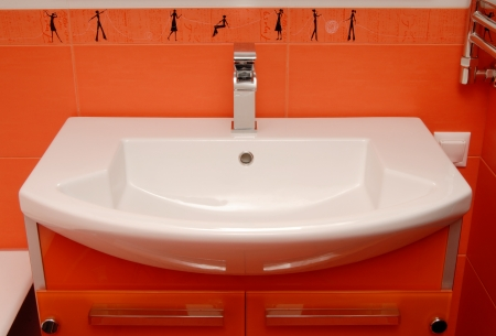 chromium plated: A modern wash-bowl is in orange  bathroom  Stock Photo