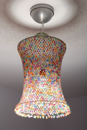 A coloured lampshade is out of netting  and beads  photo