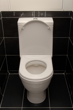 The white toilet bowl is in black interior  photo