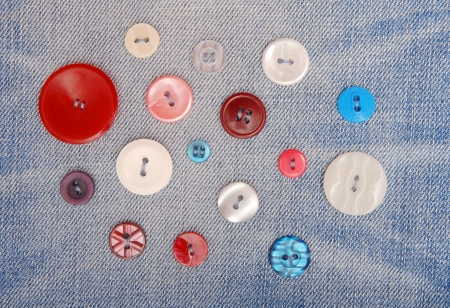 fancywork: Variegated buttons are sewn on denim  Stock Photo