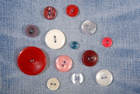 Variegated buttons are sewn on denim  photo